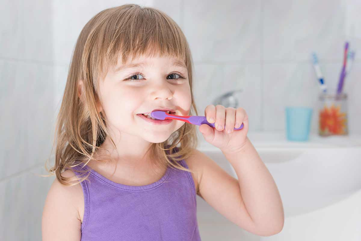 Photograph of a happy young girl brushing her teeth
