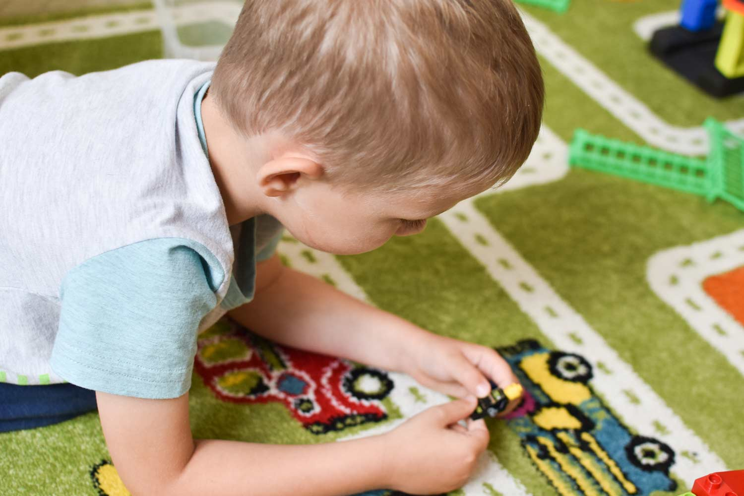 Photo of a preschool child playing with toy cars on the floor