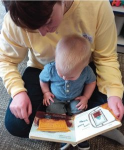 A teacher reading a book to an infant in our infant child care program