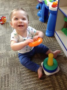happy infant playing at Memories and Milestones Academy